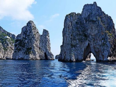 A boat sails through a spectacular rock formation on our private boat tour around Capri.