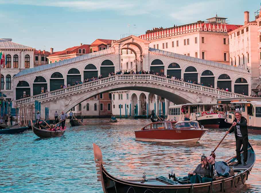 a couple take a selfie on a gondola tour with a Venetian boatman.