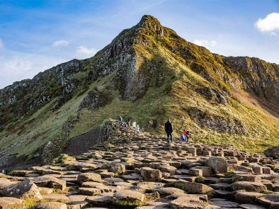 tour guests standing on the rock formations at the giant's causeway in Ireland.