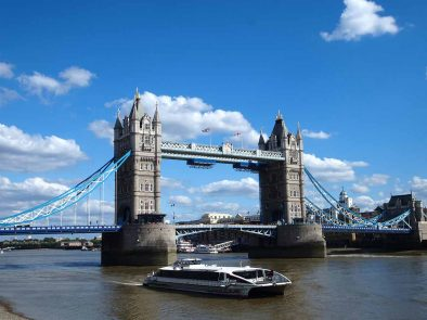 Enjoying a river cruise along the Thames with London Bridge in the background.